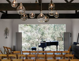 Located in the renovated barn, the living room can be transformed into a performance space that seats 80. The art piece is from South Africa. Accompanying the Steinway piano is a sideboard from Restoration Hardware; the pendants are from Cisco Home.