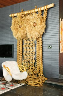 "Andy Harman's macrame Owl punctuates the living room with a California-craft sensibility while the midnight-blue brick imbues the space with a ""German-Brutalist-1960s kind of feel,"" says Adler. ""It gives the room a nice architectural gravitas."""
