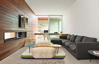 """In the lounge, a sofa from Flexform joins a rug and poufs from Gandia Blasco. """"We used boulders found onsite in the walls and windows as a way to reinforce the home's connection with the desert environment,"""" Lockyer explains. As throughout, the wall and ceiling are painted with Cool December from Dunn-Edwards."""