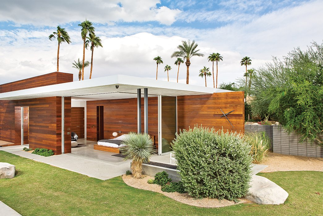 Exterior, Wood Siding Material, House Building Type, and Flat RoofLine The master bedroom opens on two sides to the outdoors, where Lockyer placed a custom black-chrome wall clock.  Photo 10 of 13 in One Canadian Family Beats the Cold by Escaping to Palm Springs