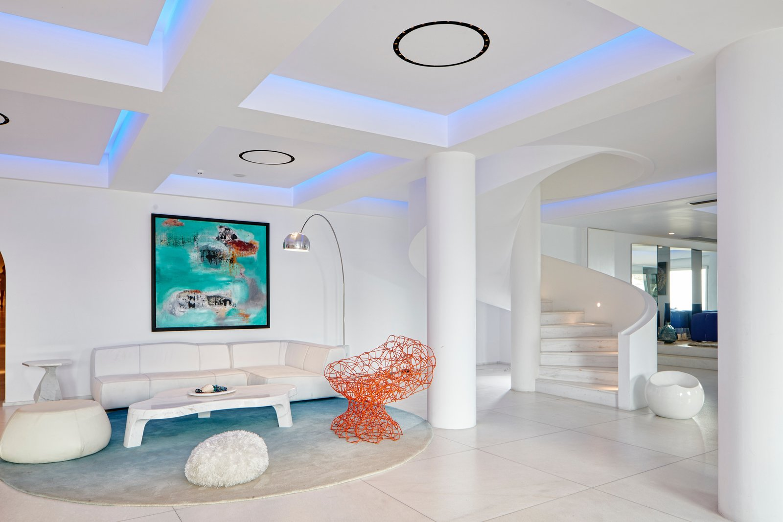 Pillars and a spiral staircase act as modern interpretations of ancient Greek design themes. The orange Coralla chair was designed by the Campana Brothers for Edra and makes a sculptural statement. Tagged: Living Room, Accent Lighting, Floor Lighting, Chair, Ottomans, Rug Floor, Sectional, and Coffee Tables.  Photo 7 of 12 in This Revived Greek Resort Will Soon Be at the Top of Your List