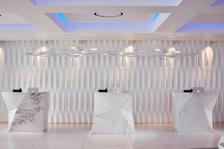 When you proceed to check in, you'll see that Mahmoud had large blocks of solid Thassos marble carved into sharp geometric shapes to contrast against the more classic, softer lines—each one weighs over five tons. The sculpted wall is inspired by the marble draperies of the antique statues of Delos.