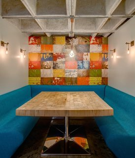 The studio created a breakfast nook with a colorful mural in the heart of the home. The metal sconces are custom.