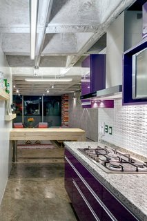 Synthetic, organic, and industrial materials coexist in the kitchen. The cabinets are finished in aubergine-purple polyester, the breakfast bench is made of an upcycled timber beam, and the range hood is steel.