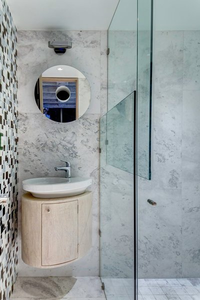 Rich Veracruz marble lines one wall of the bathroom, black-and-white tiles of various sizes clad another.