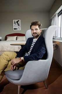 """Jaime Hayon is Given the Keys to an Iconic Copenhagen Hotel - Photo 2 of 9 - Hayon sits in the Ro armchair he designed for Fritz Hansen, one of the items he placed in the room. """"As an artist and a furniture designer, I focus on the small elements rather than the big space,"""" he says. """"If you're comfortable on your chair, and it feels good, that's a really good starting point to have a successful space. Then I focus on the rest of the room in terms of color, ambiance, and lighting."""""""