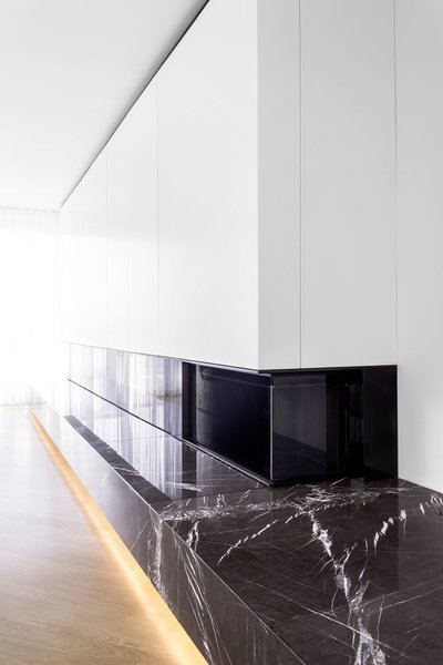 A custom unit around the fireplace conceals cabinets and shelves.