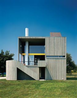 The wood-frame residence and studio are clad in vertical cedar siding—back then, a daring competitor to clapboard—instead of concrete to save costs. The effect is equally seamless, however: '' If you drive by it fast enough,'' Charles Gwathmey once said, ''you still might mistake it for a concrete house''