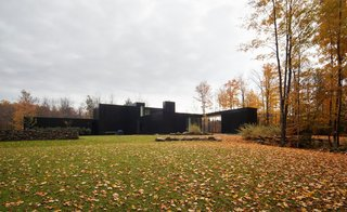 The black-lacquered aluminum panels and double-height volumes of this home in southern Quebec, designed by Les Architectes FABG, abstract its scale from the outside.