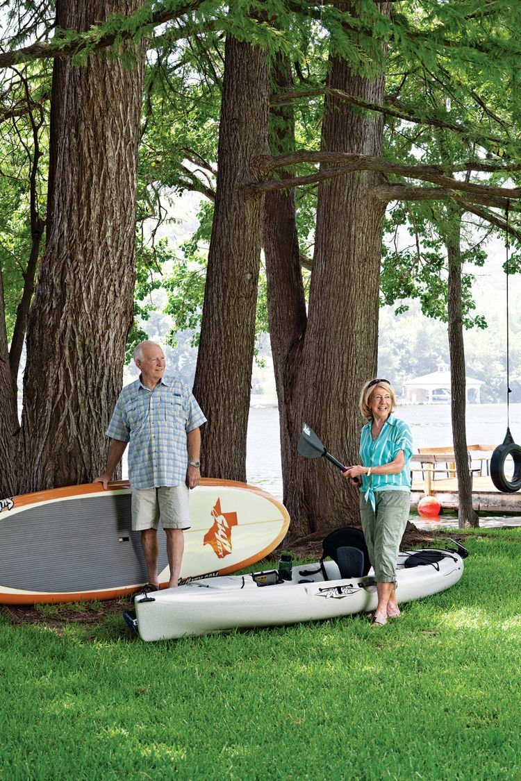 Owners Dudley and Sandy Youman keep a flotilla of watercraft ready for entertaining their children and grandchildren. Interior designer Herb Schoening worked with the Youmans on the furnishings and finishes for the their 480-square-foot-cabin.  Photo 3 of 7 in The Lakeside Getaway That Entertains All Ages