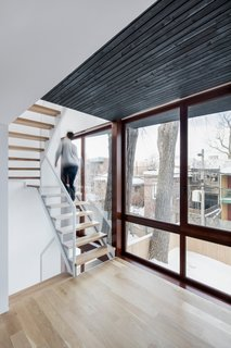 The expansion creates a narrow intermediary space between the yard and existing home. This sliver contains a light steel staircase and two new sun rooms for reading.