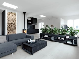 "The living features a sofa from Engell; a suspended Parentesi lamp by Achille Castiglioni and Pio Manzù for Flos (Olsen's ""all-time favorite.""); and a wood-burning stove made by Aduro. The firewood nook set in the left wall is Jensen's own design. Olsen is responsible for the low planters around the perimeter, which she had fabricated from poured concrete framed in welded iron, with lacquered MDF panels for doors. ""Some people laughed because we;d never had plants in our apartment,"" she says. ""So when we wanted a hedge, our friends were, like Ok. Really? Good luck with that."""