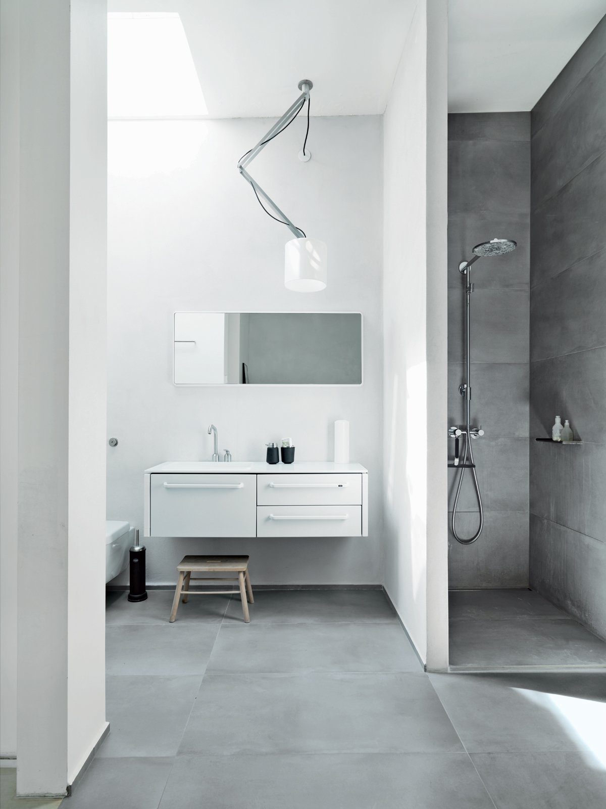 The family shares one main bathroom, which is outfitted with pieces from Vipp: 982 bath furniture, a 906 faucet, and a 992 mirror. The shower sports a Raindance connect showerhead by Hansgrohe, and there is a wall-mounted toilet by Villeroy & Boch. The Nomad light fixture is from Modular Lighting Instruments, and the floors are topped with ceramic tiles by LaFrenza.  Photo 8 of 8 in Two Designers Sharpen Up This Former Pencil Factory