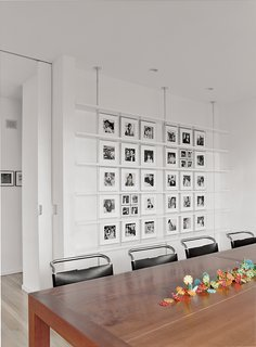 In the dining room, Mies van der Rohe chairs surround a custom-made cherry table. Black-and-white photographs of Sasseen's children and grandchildren are arranged systematically on the back wall.