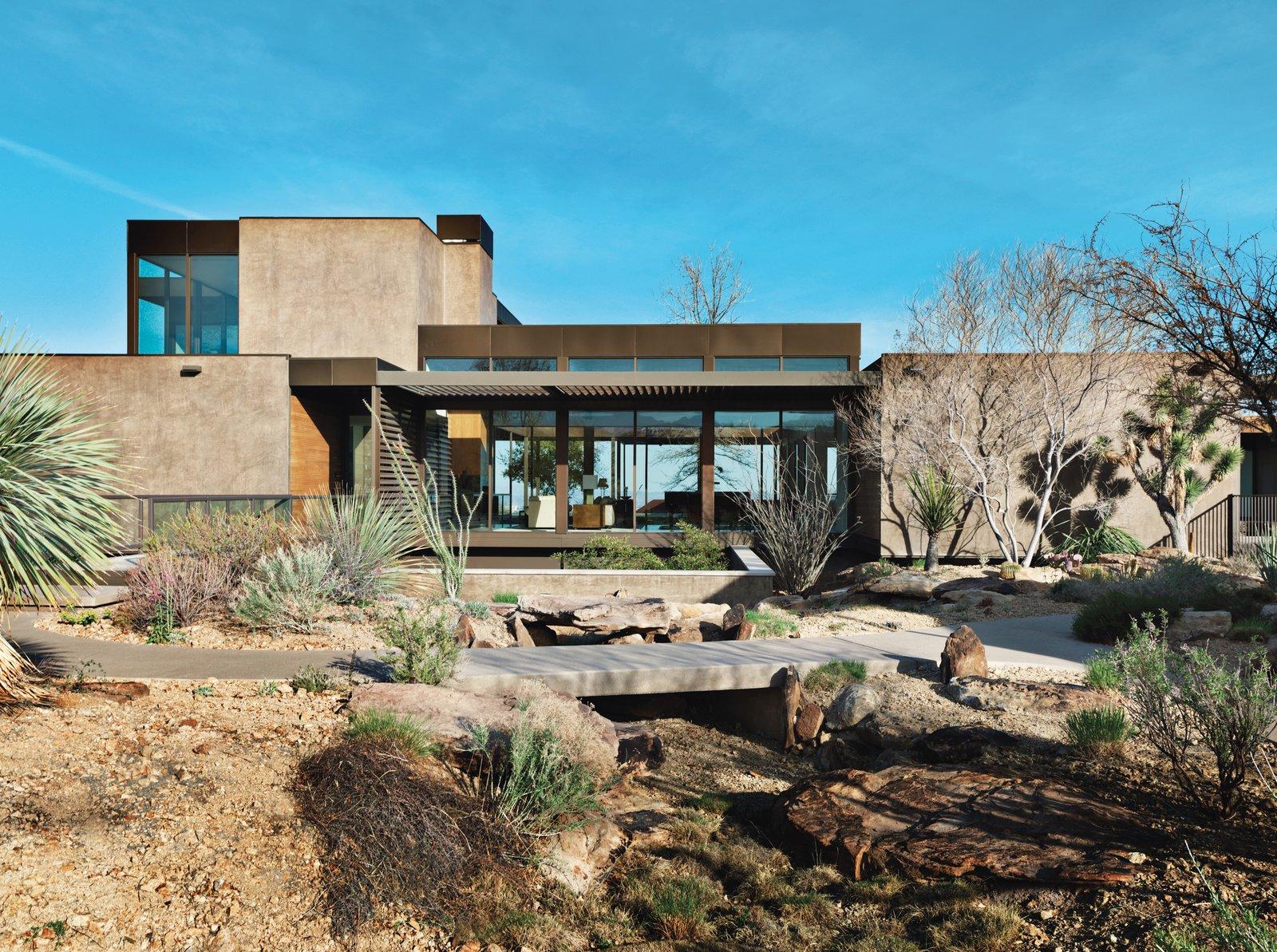 Las Vegas Desert Prefab Home concrete exterior with desert plant landscaping and concrete patio bridge walkway