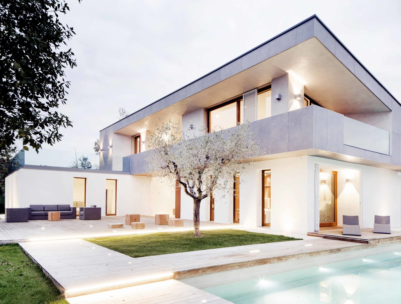 Outdoor, Back Yard, Trees, Grass, Swimming Pools, Tubs, Shower, Wood Patio, Porch, Deck, and Landscape Lighting In seaside Tuscany, Italian architecture firm FABBRICANOVE realized a villa that embraces modern lines and the mild climate.  Photo 2 of 5 in Pulling off Mediterranean Modern in Tuscany