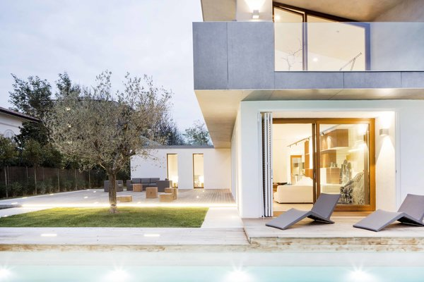 A lap pool and protected courtyard with a lone tree flank the home.