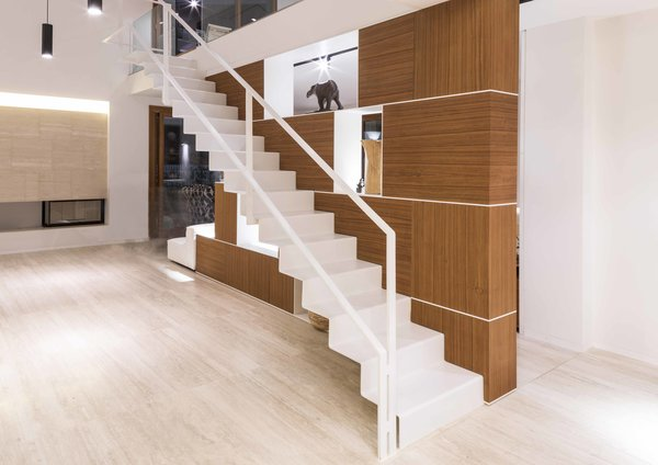 A thin floating staircase rises to the second floor almost weightlessly.