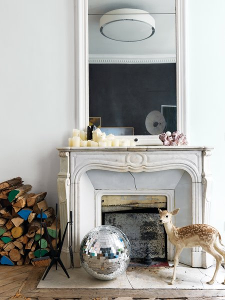 Aumas created a series of vignettes throughout the apartment that are playful and unexpected, mixing fun elements with practical and historic details. Here, an original marble fireplace is paired with a disco ball, a stuffed fawn, and firewood that's selectively been painted in bright colors.