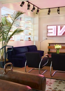 A comfortable seating area is situated a couple of steps into the hotel. The navy-blue sofa is ASH's design and the vintage armchairs with chrome handles are by Jindrich Halabala. Iron Origami fabricated the square coffee table just past the chairs. Artist Oliver Clegg created the neon sign.
