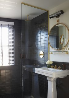 The bathrooms are clad in black Daltile and feature brass hardware from Watermark in the European-style shower and on the sink. The mirror is custom. ASH worked with American Medicinal Arts on the custom-scented toiletries.