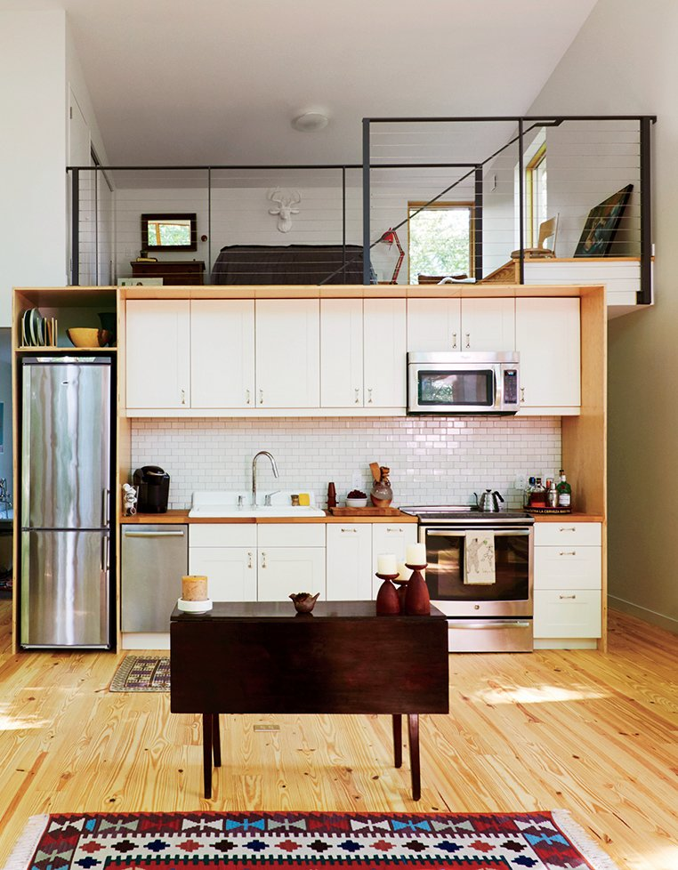 The kitchen and lofted guest bedroom take cues from urban living—including an apartment-size Summit refrigerator. The cabinets are IKEA and the tile is by Heath Ceramics.  Photo 7 of 11 in Make Your Space Look Bigger: 10 Lofted Bedrooms from A Little Cabin Reaches Such Great Heights