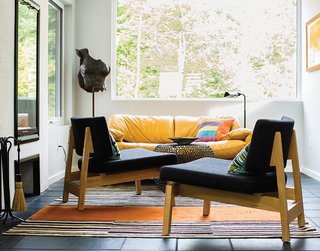 "One end of the gathering hall is furnished with a pair of lounge chairs and an iron side table, all from CB2 and since discontinued. Brogan designed the rug and had it made at the Mehmet Çetinkaya Gallery in Istanbul. Brogan says she chose the Maralunga sofa by Vico Magistretti for Cassina ""for the color and the scale in a small area near the tiny fireplace."""