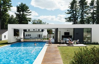 A prefab pool and guesthouse designed by LABhaus frames views of a Massachusetts property's original structure, a Dillman model Sears Roebuck kit house from 1928.