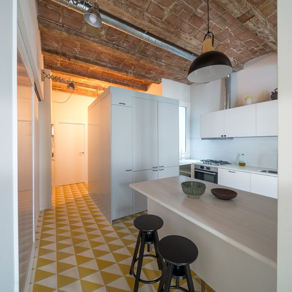 The most striking feature of the original apartment was the vaulted ceilings with wood beams, which were kept intact. A geomteric hydraulic mosaic flooring covers the kitchen.