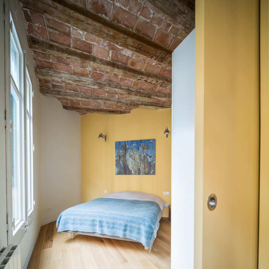 The apartment, approximately 765 square feet in total, contains one master bedroom as well as a smaller sleeping space for guests. A sliding door closes off the bedroom from the living area when total privacy is desired.  Photo 6 of 6 in In Barcelona, Vaulted Ceilings Are Always a Win