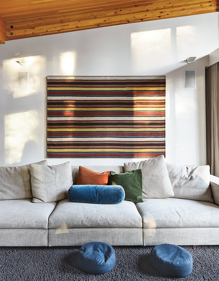 In the living room, an 18th century jajim, purchased in Istanbul, hangs behind a Molteni & C sofa covered in woven linen with mohair pillows. The wool rug is from California Carpets.  Photo 2 of 11 in The Ski Retreat for All Seasons