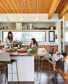 The Ski Retreat for All Seasons - Photo 2 of 10 - In the kitchen, designer Maca Huneeus prepares lunch with her daughters Ema, 12, and Ofelia, 7. The pendants are Jonathan Adler; the island is a custom design, inspired by a 1960s Dansk tray that belonged to Huneeus's mother. The barstools are from Blu Dot.