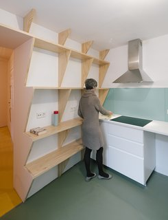 At just under 1,400 square feet, the three-bedroom apartment benefits from built-in space savers including sawtooth shelving and even a fold-out bench.