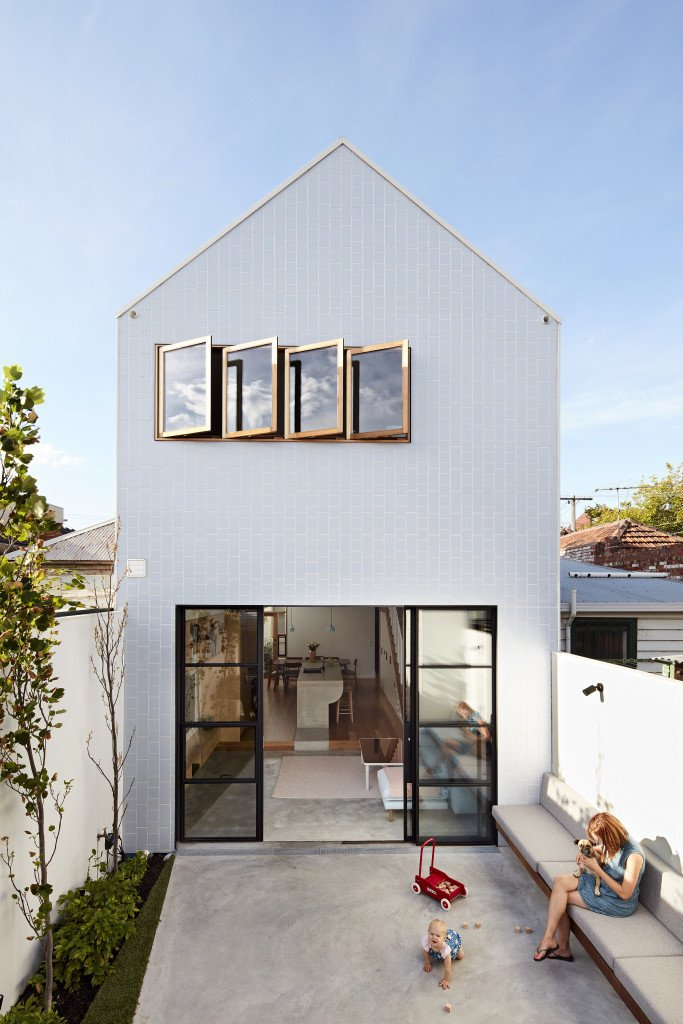 The Scyon Axon cladding of this gabled Melbourne addition gleams at midday. Designer Dan Gayfer punctuated the facade with sliding glass doors and a row of windows to fill the narrow home with sunlight. Tagged: Outdoor, Small Patio, Porch, Deck, Back Yard, and Concrete Patio, Porch, Deck.  Photo 2 of 11 in It Looks Like a Playland but This Home Works Hard