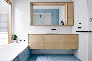 Each of the home's bathrooms displays a different eye-catching shade of tile from Inax, such as baby blue.