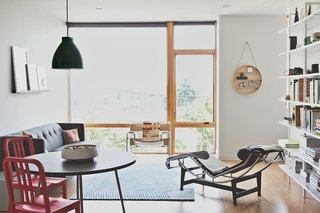 Bowie and Malboeuf's unit occupies three levels facing the property's backyard. The living-dining room has a mix of vintage pieces—a Wassily chair by Marcel Breuer and an LC4 chaise by Le Corbusier, Pierre Jeanneret, and Charlotte Perriand—alongside furniture from CB2.
