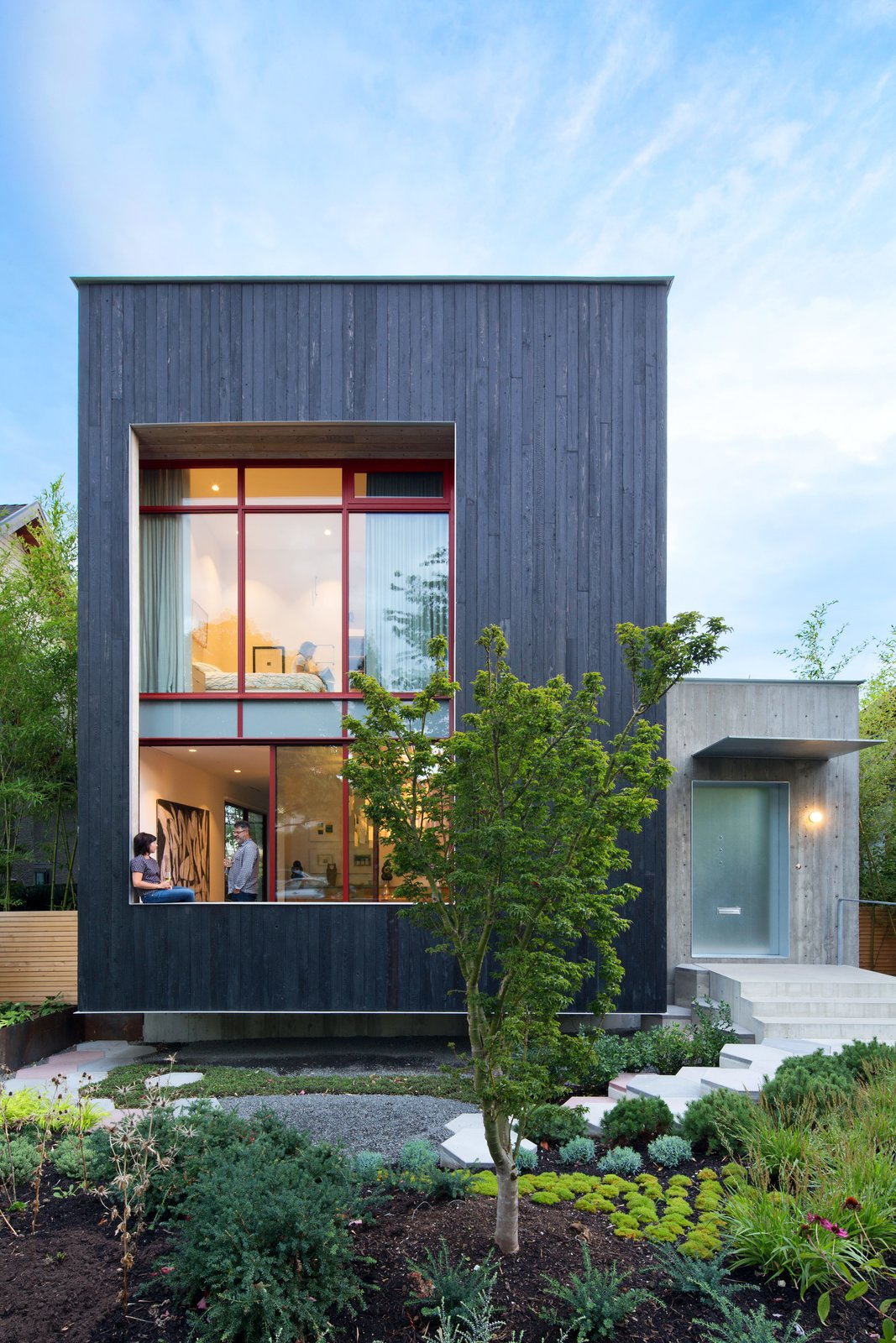 The street-facing facade leans into the landscape with a three-foot-deep cantilever and toward a pathway of hexagonal concrete pavers. Tagged: Front Yard, Trees, Walkways, Exterior, Wood Siding Material, and House.  Photo 5 of 5 in A Wild Garden Leaps Off the Walls of This Backyard Build