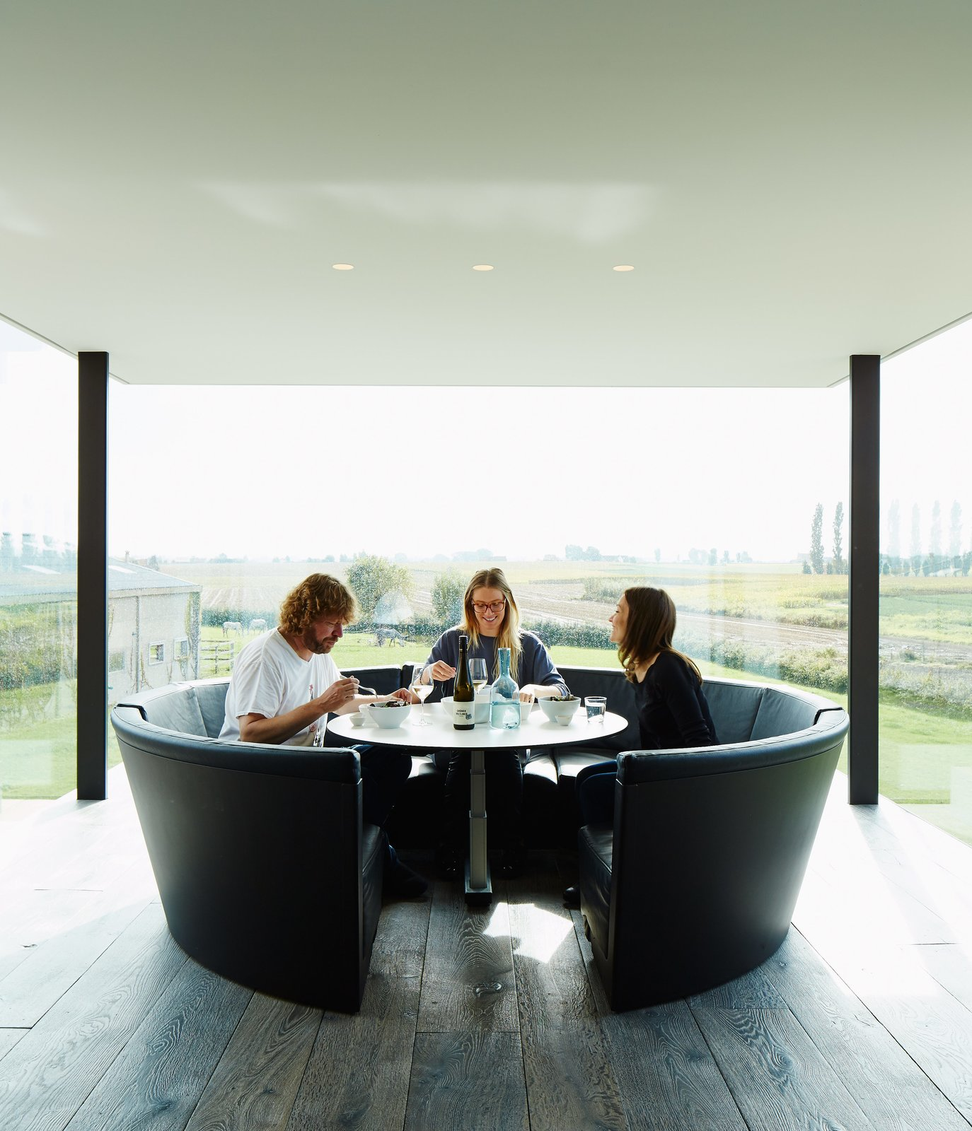 Dining Room, Table, Recessed Lighting, Dark Hardwood Floor, and Bench Wynants lives in the house with his wife, Hilde Louwagie, and their three children. His own circular seating design, Kosmos, is in the kitchen.  Photo 3 of 11 in A Kubrick-Esque Farmhouse Kicks Its Fossil Fuel Habit