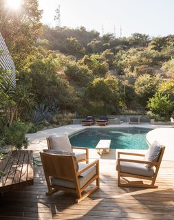 Low retaining walls form a subtle barrier between the backyard and the surrounding vegetation. Mandy Graham designed the armchairs and lounges.