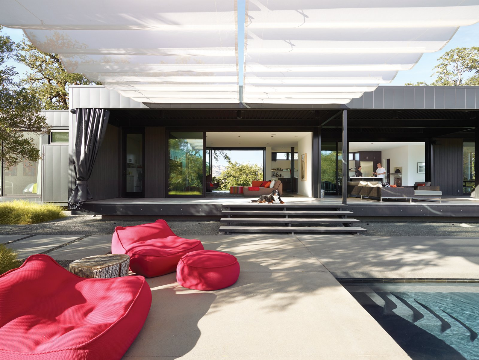 In the foreground are Float beanbag chairs and poufs from Paola Lenti. Mamagreen sofas nestle near the house on the sun-dappled deck. A 9.5-foot-tall shade cloth curtain seals off the entire length of the house when the couple is away, keeping the heat out of the interior and preventing accidental bird suicides against the floor-to-ceiling glass walls.  Photo 3 of 8 in When Prefab Is Painless