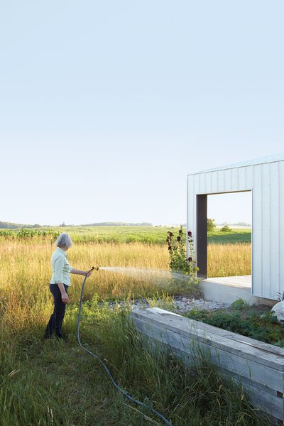 Outdoor and Gardens Maggie Treanor waters plants around her rural home.  Photo 4 of 11 in An Off-Grid Home That Relies on the Sun and the Wind