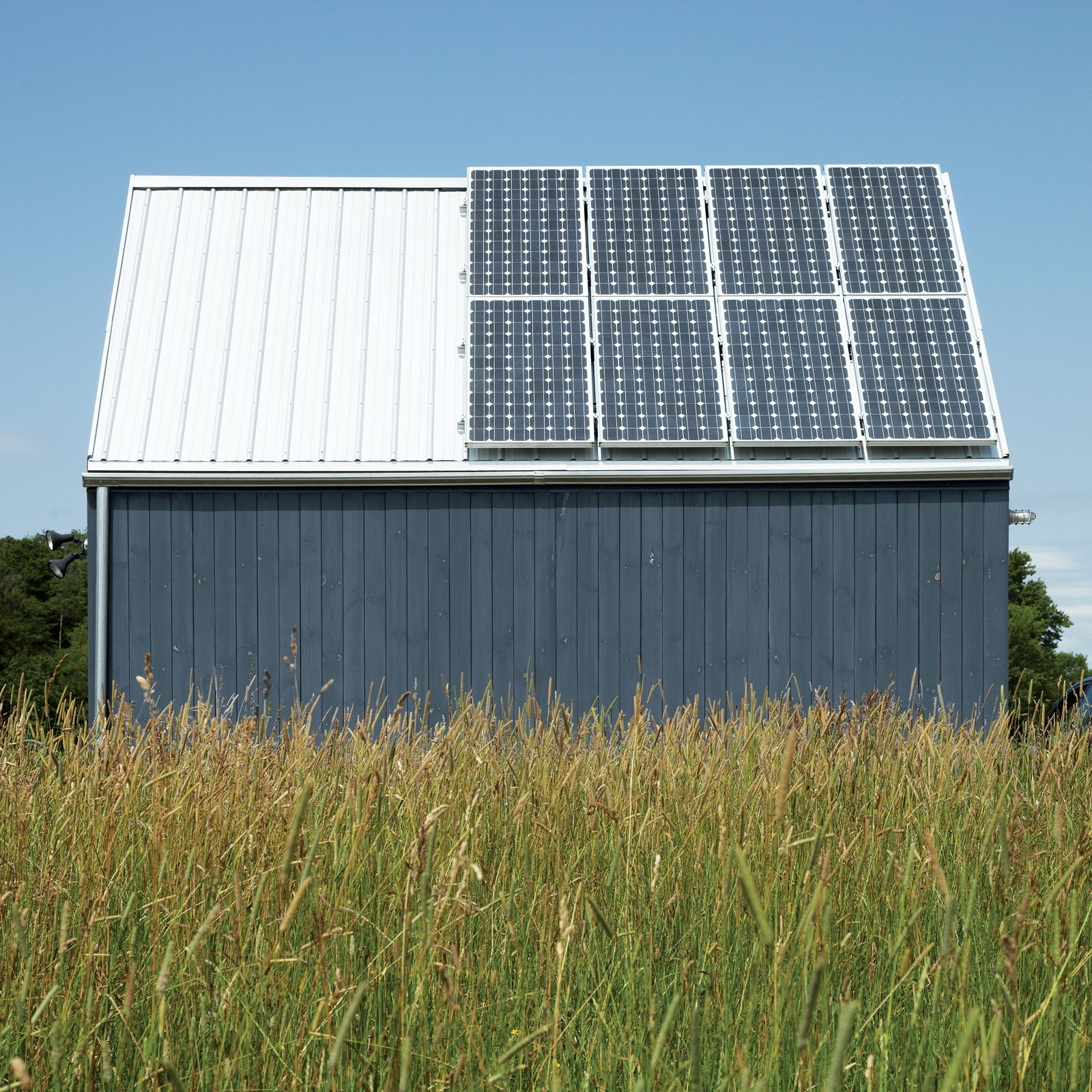 Exterior, Gable RoofLine, Metal Siding Material, and House Building Type A 1.4-kW solar array by Sharp and propane-powered in-floor radiant heating from Radiantec obviate any need to connect to municipal power.  Photo 8 of 11 in An Off-Grid Home That Relies on the Sun and the Wind