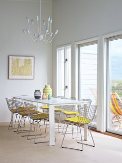A Single Octopus chandelier by Autoban hangs above a Four dining table by Ferruccio Laviani for Kartell and a set of side chairs by Harry Bertoia for Knoll.