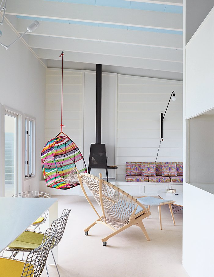 Living Room and Chair Alexandra Angle transformed a beachside cabin into a colorful retreat for a college friend and her family. The living area features a PP130 Circle Chair by Hans Wegner and a Shaker wood stove by Antonio Citterio with Toan Nguyen for Wittus. A Tropicalia Cocoon hanging chair by Patricia Urquiola complements the fabric from Liberty that Angle used for the cushions on the built-in banquette.  Photo 4 of 9 in How a Smart Interior Design Saved This House