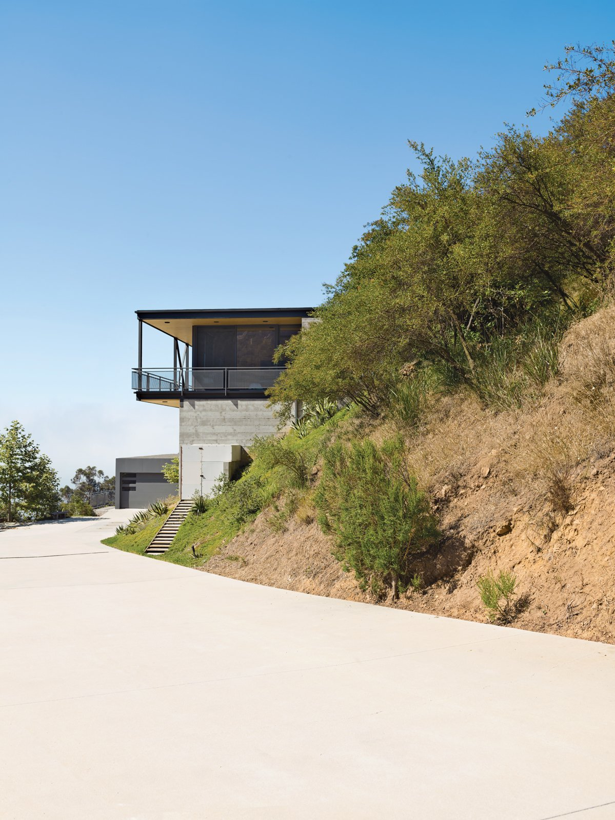 Exterior, House Building Type, Concrete Siding Material, and Flat RoofLine To deal with a Malibu site's sharp incline, architect Bruce Bolander set the steel, concrete, and glass house on caissons. A deep wraparound porch nearly doubles the home's living space and offers the ideal perch for outdoor dining and taking in spectacular views of the surrounding canyon. The garage serves as resident Dave Keffer's home office.  Photo 2 of 9 in This High-Flying Home Tackles a Sharp Slope