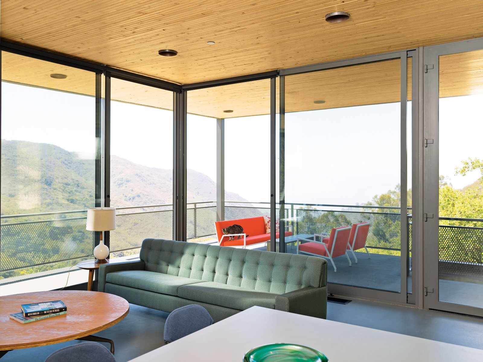 Living Room, Chair, Sofa, and Coffee Tables The sofa and lights in the open-plan living, dining, and kitchen area are vintage.  Photo 7 of 9 in This High-Flying Home Tackles a Sharp Slope