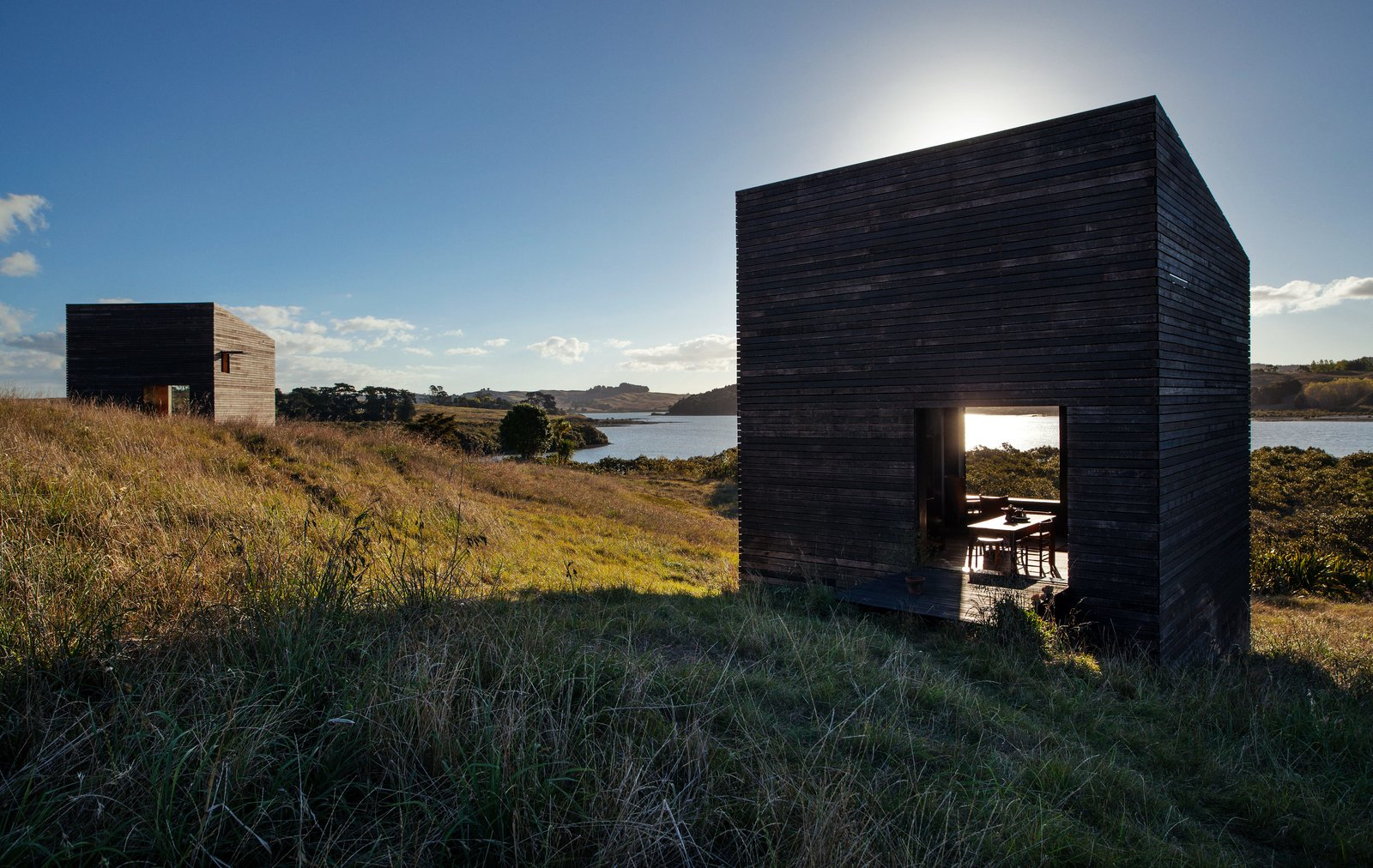 Shed & Studio and Living Space Room Type Before building on the North Island of New Zealand, two friends spent years replanting the site. The 290-square-foot structures Cheshire Architects designed for them reject the local trend of oversize beach houses—instead, they sit on the landscape like a pair of minimalist sculptures.  Photo 2 of 7 in Two Tiny Cabins Chose Simplicity Over Size