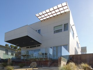 This pair of detached houses on one lot in an urbanized area of San Diego embraces its seaside setting with a series of courtyards that usher in the ocean breeze. The houses are remarkably efficient thanks to a combination of passive and active strategies, including a concrete-board rain screen for temperature regulation and photovoltaic arrays for solar energy.