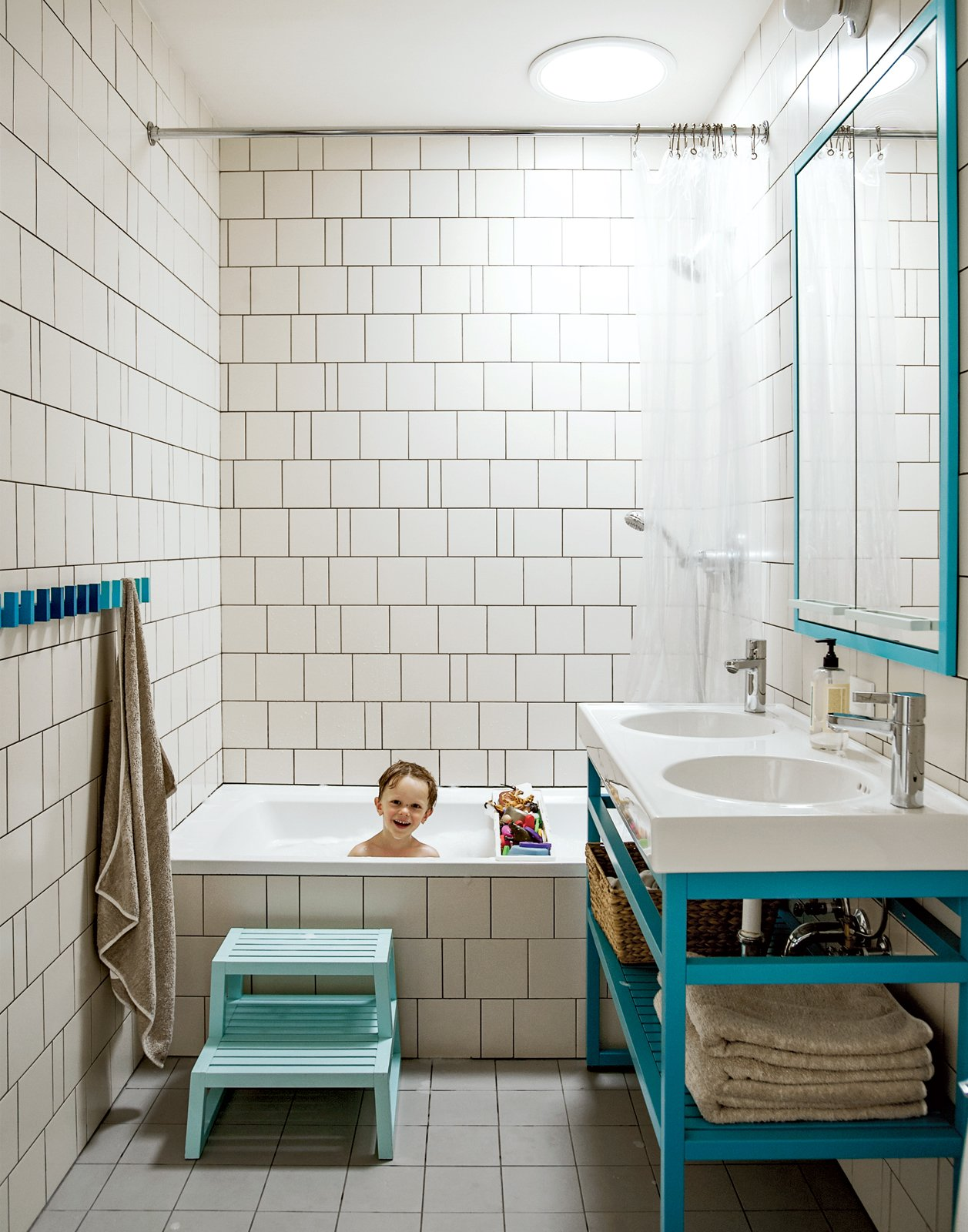 """Bath Room, Porcelain Tile Floor, and Drop In Tub A creative way of cutting costs is on display in son Nate's bathroom, where the wall tiles are arranged in a whimsical, irregular pattern making use of slim sections of tile cut for transitions and corners. """"We came up with a pattern that could incorporate random sizes so we were able to order the exact amount of tile that we needed,"""" Bischoff says. """"It allowed us to get the most out of the tile price because there wasn't that 20 percent that [would normally go] into the landfill."""" The two-bowl sink is the Vitviken model from Ikea; it's topped with a chrome Hansgrohe faucet and accented by Ikea's Godmorgon medicine cabinets customized by MADE.  Photo 7 of 9 in The Brownstone Baked to Perfection"""