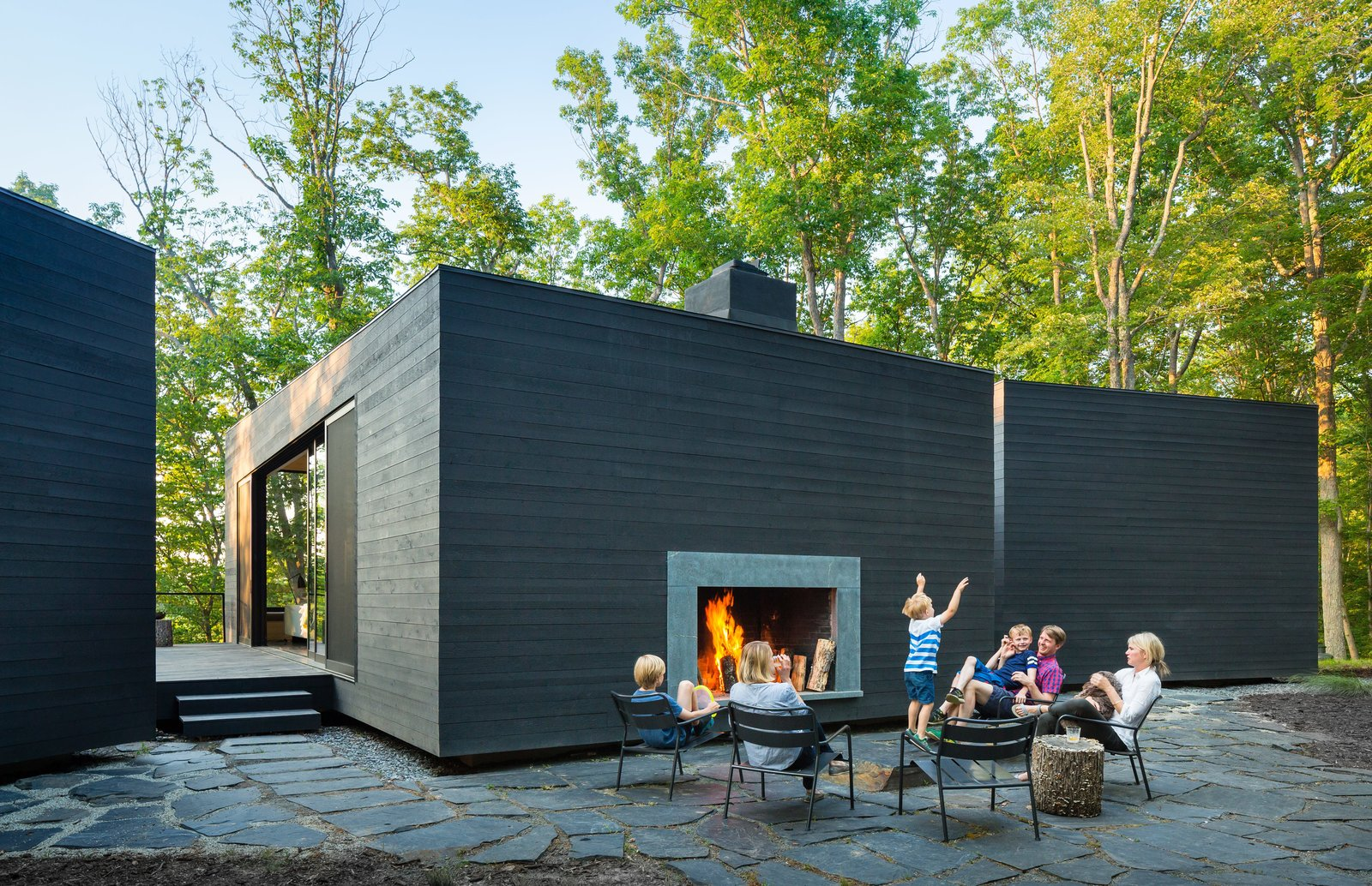 Unlike the north-facing side of the home, the south-facing facade is completely windowless and opaque, with the exception of an outdoor hearth built directly into its side. The lounge chairs are from IKEA, and the MacNellys sourced the slate flagstones and gravel surrounding the home from a local quarry.  Photo 8 of 9 in Three Joined Cabins Turn This Virginia Retreat Into a Modern Take on Camp